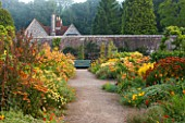 WEST DEAN GARDENS, WEST SUSSEX: LATE SUMMER BORDERS IN THE WALLED VEGETABLE GARDEN - PATH TO SEAT / BENCH - ORANGE THEMED BORDER - HOT, WARM, FLOWER, FLOWER BEDS