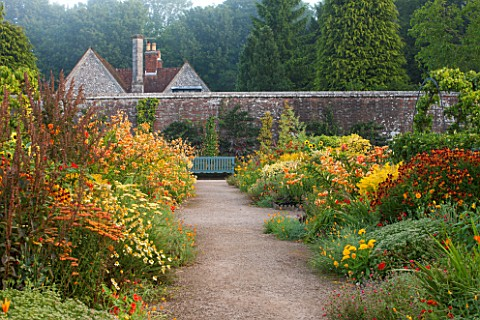 WEST_DEAN_GARDENS_WEST_SUSSEX_LATE_SUMMER_BORDERS_IN_THE_WALLED_VEGETABLE_GARDEN__PATH_TO_SEAT__BENC