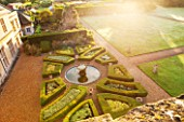 LAMPORT HALL, NORTHAMPTONSHIRE: AERIAL VIEW LOOKING DOWN ONTO THE ITALIAN GARDEN WITH BOX PARTERRES, GRAVEL PATHS AND FOUNTAIN. FORMAL, HISTORIC, CLASSIC ENGLISH GARDEN