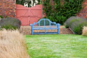 LAMPORT HALL, NORTHAMPTONSHIRE: THE WALLED CUTTING GARDEN / KITCHEN GARDEN: BLUE BENCH BESIDE GRASS PATH WITH WALL AND GATE BEHIND. SUMMER