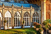 SEZINCOTE, GLOUCESTERSHIRE: THE MAGNIFICENT CURVING ORANGERY WITH CONTAINERS OF FUCHSIAS OUTSIDE IN MORNING LIGHT