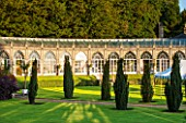 SEZINCOTE, GLOUCESTERSHIRE: THE MAGNIFICENT CURVING ORANGERY WITH CONTAINERS OF FUCHSIAS OUTSIDE IN MORNING LIGHT - TENT AND IRISH YEWS