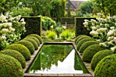 WOLLERTON OLD HALL, SHROPSHIRE: THE RILL GARDEN WITH CANAL, CLIPPED BOX, HYDRANGEAS IN CONTAINERS, STANDARD CARPINUS BETULUS FRANS FONTAINE. SYMMETRY, CLIPPED, TRIMMED, SHAPED