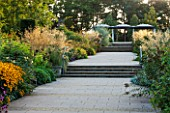 RHS GARDEN, WISLEY, SURREY: THE BOWES - LYON ROSE GARDEN WITH PLANTING OF ROSES AND STIPA GIGANTEA IN SUMMER - SEPTEMBER - EVENING LIGHT - PATH