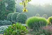 SURREY GARDEN DESIGNED BY ANTHONY PAUL: MISTY MORNING WITH CLIPPED PRUNUS LUSITANICA - PORTUGAL LAUREL, HOUSE AND GRASSES. SUMMER, MIST, COUNTRY GARDEN,