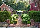 SURREY GARDEN DESIGNED BY ANTHONY PAUL: VIEW TO BRICK TERRACE WITH BEDS OF WHITE HYDRANGEA ANNABELLE - PATIO, SUMMER, COUNTRY GARDEN, FORMAL, SEPTEMBER