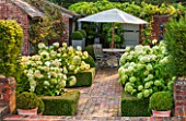SURREY GARDEN DESIGNED BY ANTHONY PAUL: VIEW TO BRICK TERRACE WITH BEDS OF WHITE HYDRANGEA ANNABELLE AND TABLE AND CHAIRS - PATIO, SUMMER, COUNTRY GARDEN, FORMAL, SEPTEMBER