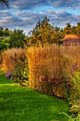 RYE HALL FARM, YORKSHIRE - DESIGNER SARAH MURCH - COUNTRY GARDEN IN AUTUMN, OCTOBER - LAWN AND BORDER WITH GRASSES - CALAMAGROSTIS X ACUTIFLORA KARL FOERSTER AND SEDUM MATRONA