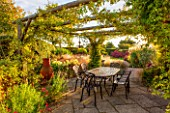 RYE HALL FARM, YORKSHIRE - DESIGNER SARAH MURCH - COUNTRY GARDEN IN AUTUMN, OCTOBER - PERGOLA WITH PATIO, METAL TABLE AND CHAIRS, A PLACE TO SIT, HYDRANGEA ANNABELLE, EATING