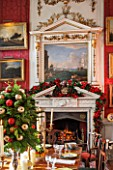 CASTLE HOWARD, YORKSHIRE: CHRISTMAS - THE CRIMSON DINING ROOM DECORATED FOR CHRISTMAS WITH CANDLES AND CHRISTMAS DECORATIONS - DECORATIVE, ORNAMENT, WINTER, NOVEMBER, FIREPLACE