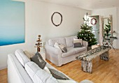 SALTWATER, NORFOLK : DESIGNER KAREN MOORE - CHRISTMAS, DECEMBER, WINTER - WHITE LIVING ROOM WITH ALUMINIUM PHOTOGRAPH BY HARRY CORY WRIGHT, SETTEE, WOODEN BENCH AND CHRISTMAS TREE