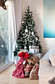 SALTWATER, NORFOLK : DESIGNER KAREN MOORE - CHRISTMAS, DECEMBER, WINTER - WHITE LIVING ROOM WITH ALUMINIUM PHOTOGRAPH BY HARRY CORY WRIGHT, CHRISTMAS PRESENTS AND CHRISTMAS TREE