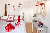 SALTWATER, NORFOLK : DESIGNER KAREN MOORE - CHRISTMAS, DECEMBER, WINTER - BEDROOM IN RED AND WHITE - BED WITH STOCKINGS ON WALL, TOY BOAT AND REINDEERS, ORNAMENT