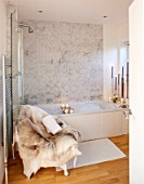 SALTWATER, NORFOLK : DESIGNER KAREN MOORE - CHRISTMAS, DECEMBER, WINTER - BATHROOM IN WHITE AND GREY - CHAIR WITH REINDEER SKIN, CANDLES, ORNAMENT, DECORATION, LIGHTING, BATH