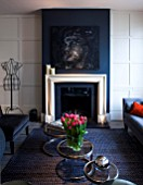 SALLY STOREY HOUSE, LONDON: OPEN PLAN SITTING ROOM / HALL WITH FIREPLACE, PAINTING BY SALLYS DAUGHTER LUCCA, SETTEE, CHAIRS, RUG, LIGHT, CHIMNEY PAINTED IN FARROW & BALL DOWNPIPE