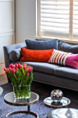 SALLY STOREY HOUSE, LONDON: OPEN PLAN SITTING ROOM / HALL WITH GREY SETTEE, RUG AND GLASS TABLE WITH TULIPS IN VASE, CUSHIONS, SHUTTERS