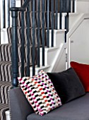 SALLY STOREY HOUSE, LONDON: OPEN PLAN SITTING ROOM / HALL WITH GREY CHAIR WITH CUSHIONS - BLACK AND WHITE STAIRCASE, STAIRS