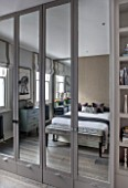 SALLY STOREY HOUSE, LONDON: MASTER BEDROOM WITH BED, CUSHIONS AND SIDEBOARDS REFLECTED IN THE MIRRORED WARDROBE - MIRROR