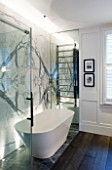 SALLY STOREY HOUSE, LONDON: WHITE AND GREY BATHROOM WITH BOOKMATCHED MARBLE WALL, BATH AND TOWEL RAIL - LIT, LIGHT, LIGHTING, LIGHTS