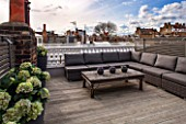 SALLY STOREY HOUSE, LONDON: ROOF TERRACE WITH FAKE WOODEN DECKING, LOUNGERS AND WOODEN TABLE. FAKE HYDRANGEAS, ROOF GARDEN, SEAT, SEATS, ENTERTAINING, DECK, TOWN GARDEN, MODERN