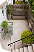 DESIGNER STEPHEN WOODHAMS, LONDON: FORMAL TOWN GARDEN IN SPRING - BASEMENT, TERRACE WITH CONTAINERS AND METAL SEATS. STEPS, STAIRS, STAIRWAY, TRELLIS, BOX, BUXUS, PAVING