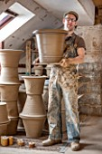 WHICHFORD POTTERY, WARWICKSHIRE: ADAM KEELING HOLDING NEWLY HANDMADE TERRACOTTA CONTAINER IN THE WORKSHOP