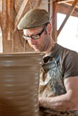 WHICHFORD POTTERY, WARWICKSHIRE: ADAM KEELING THROWING A NEWLY HANDMADE TERRACOTTA CONTAINER IN THE WORKSHOP