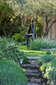 LA JEG, PROVENCE, FRANCE: DESIGNER ANTHONY PAUL - STONE STEPS PAST ROSEMARY TO SCULPTURE BY HELEN SINCLAIR. FRANCE, ORNAMENT, MEDITERRANEAN, FORMAL, GARDEN