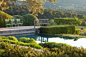 LA JEG, PROVENCE, FRANCE: DESIGNER ANTHONY PAUL - SWIMMING POOL AND DECK WITH CLIPPED TOPIARY. MAY, MEDITERRANEAN, WATER, GARDEN, FORMAL, POND, DECKING, DECKED