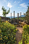 LA JEG, PROVENCE, FRANCE: DESIGN: ANTHONY PAUL - PATH, PHLOMIS, SCULPTURE - SILENT COLUMNS BY CHRIS BOOTH, WALL, STONE, SUMMER,  COUNTRY, GARDEN