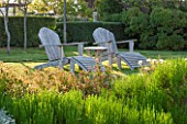 LA JEG, PROVENCE, FRANCE: DESIGNER ANTHONY PAUL -  TWO ADIRONDACK CHAIRS ON LAWN. WOOD, WOODEN, BENCH, CHAIR, A PLACE TO SIT, SPRING. MEDITERRANEAN, GARDEN, GREEN, PROVENCE, MAY
