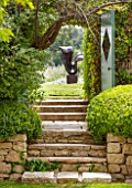 LA JEG, PROVENCE, FRANCE: DESIGNER ANTHONY PAUL - STONE STEPS AND DOORWAY WITH VIEW TO SCULPTURE LOVERS BY MARZIA COLONNA. SPRING. MEDITERRANEAN, GARDEN, GREEN, PROVENCE, MAY