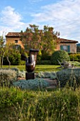 JEG, PROVENCE, FRANCE: DESIGN: ANTHONY PAUL - THE HOUSE WITH BLUE SHUTTERS. CLIPPED PLANTS BESIDE LAWN, SCULPTURE LOVERS BY MARZIA COLONNA. SUMMER,  COUNTRY, GARDEN
