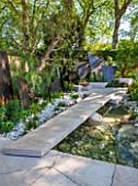 CHELSEA FLOWER SHOW 2016: TELEGRAPH GAREDEN DESIGNED BY ANDY STURGEON - LIMESTONE BRIDGE AND BRONZE FINS BESIDE WATER. LIMESTONE SEATS AND FIREPIT - SEATING, BENCH, BENCHES, PATH