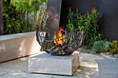 CHELSEA FLOWER SHOW 2016: TELEGRAPH GAREDEN DESIGNED BY ANDY STURGEON - LIMESTONE PATIO, BRONZE FINS AND METAL FIREPIT - SEATING, BENCH, BENCHES, FIRE