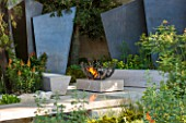 CHELSEA FLOWER SHOW 2016: TELEGRAPH GAREDEN DESIGNED BY ANDY STURGEON - LIMESTONE BRIDGE AND BRONZE FINS BESIDE WATER. LIMESTONE SEATS AND FIREPIT - SEATING, BENCH, BENCHES, FIRE