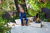 CHELSEA FLOWER SHOW 2016: TELEGRAPH GAREDEN DESIGNED BY ANDY STURGEON - ANDY STURGEON SITTING ON LIMESTONE SEAT / BENCH ON LIMESTONE PATIO, TERRACE WITH FIREPIT