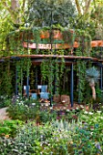 CHELSEA FLOWER SHOW 2016: THE WINTON BEAUTY OF MATHEMATICS GARDEN - DESIGNER NICK BAILEY: COPPER BAND ABOVE BELVEDERE - PATIO WITH HANGING PLANTS.