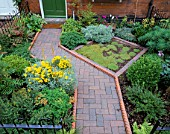 DOGLEG PATH OF BRICK AND TERRACOTTA ROPE-TWIST EDGING AND LAWN OF CORSICAN MINT. DESIGNER: JEAN BISHOP