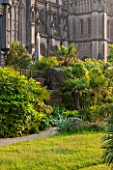 ARUNDEL CASTLE GARDENS, WEST SUSSEX: COLLECTOR EARLS GARDEN DESIGNED BY JULIAN AND ISABEL BANNERMAN. ROCKS, PATH, LAWN AND TRACHYCARPUS FORTUNEI
