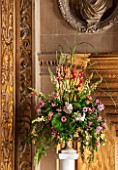CHATSWORTH HOUSE, DERBYSHIRE: FLORABUNDANCE - THE CAREFREE MANS LANDING AT THE TOP OF THE GREAT STAIRCASE. BEAUTIFUL GARDEN-GROWN FLORAL DISPLAY IN CLASSIC URN ON PLINTH