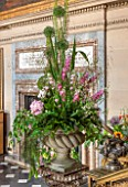 CHATSWORTH HOUSE, DERBYSHIRE: FLORABUNDANCE - THE PAINTED HALL: THE FOOT OF THE GREAT STAIRCASE WITH BEAUTIFUL FLORAL DISPLAY OF ALLIUMS AND LARKSPUR. OPULENT, GRAND, INTERIOR.