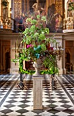 CHATSWORTH HOUSE, DERBYSHIRE: FLORABUNDANCE - THE PAINTED HALL WITH TOWERING FLORAL DISPLAY OF PEONIES AND ANGELICA ON STONE PLINTH. INTERIOR, GRAND, OPULENT.