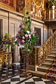 CHATSWORTH HOUSE, DERBYSHIRE: FLORABUNDANCE - THE PAINTED HALL; THE FOOT OF THE GREAT STAIRCASE. BEAUTIFUL FLORAL DISPLAY WITH ALLIUMS, PEONIES AND LARKSPUR. INTERIOR, OPULENT