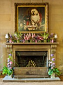 CHATSWORTH HOUSE,DERBYSHIRE:FLORABUNDANCE-THE NORTH ENTRANCE;FIREPLACE.SUMMER FLOWERS PICKED FROM THE GARDEN IN PURPLE/PINK.JARS OF LUPINS,ASTRANTIA,CAMPANULA,DIGITALIS,MINT,MILLET
