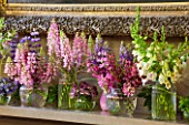 CHATSWORTH HOUSE,DERBYSHIRE:FLORABUNDANCE-THE NORTH ENTRANCE;SHELF-SUMMER FLOWERS PICKED FROM THE GARDEN IN PURPLE/PINK. JARS OF LUPINS,ASTRANTIA,CAMPANULA,DIGITALIS,MINT,MILLET