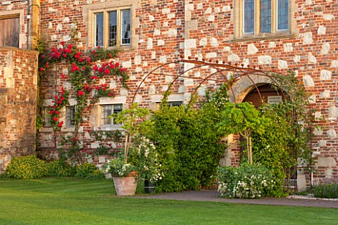 GLYNDEBOURNE_EAST_SUSSEX__RED_ROSE_GROWING_AGAINST_WALL_AND_METAL_ARCHWAY__FORMAL_ROSES_ENGLISH_SUMM
