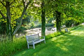 GLYNDEBOURNE, EAST SUSSEX: LAWN WITH WOODEN BENCHES AND THE LAKE I N SUMMER. WATER, POOL, TRANQUIL, PEACEFUL, COUNTRY GARDEN, LANDSCAPE