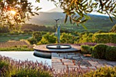 LA JEG, PROVENCE, FRANCE: DESIGNER ANTHONY PAUL - LAVENDER - LAVENDULA GROSSO - BESIDE STONE TERRACE AND SWIMMING POOL WITH SCULPTURE AND MONT VENTOUX. SUNRISE, SUMMER, JUNE