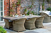 THE COACH HOUSE, SURREY: OUTDOOR PATIO AND DINING AREA WITH LARGE TABLE AND WICKER CHAIRS. SEMPERVIVUMS IN POTS ON TABLE. A PLACE TO SIT. ENTERTAIN, SUMMER, GARDEN